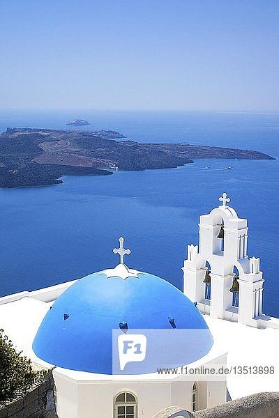 Kirche mit blauem Kuppeldach und weißem Glockenturm am Kraterrand  dahinter die Vulkaninsel Nea Kameni  Firofestani  Thira  Santorin  Kykladen  Ägäis  Griechenland  Europa