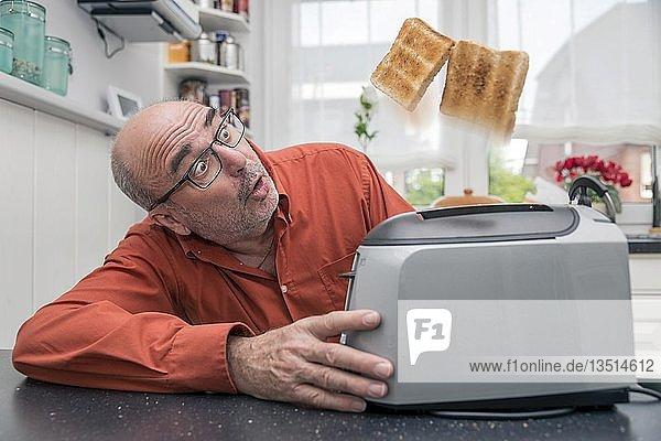 Ein Mann beobachtet  wie 2 Toastscheiben aus dem Toaster springen  Deutschland  Europa