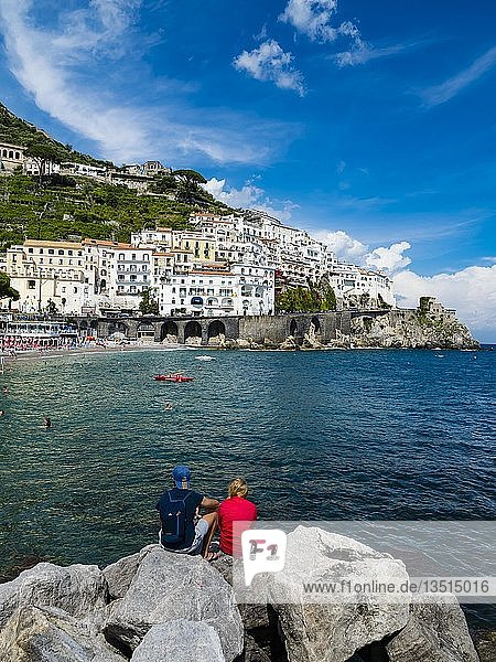 Couple sits on rock and looks at old town and beach of Amalfi  peninsula of Sorrento  Amalfi coast  Campania  Italy