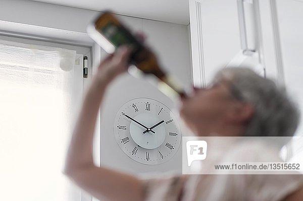 Alkoholabhängige Frau trinkt am hellichten Tag eine Flasche Bier