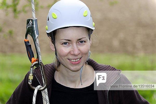 Junge Frau mit Schutzhelm und Kletterseil