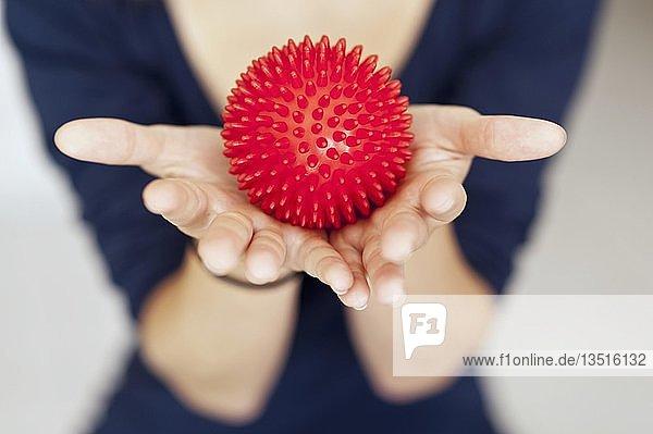 Roter Massageigel in den Händen einer Frau