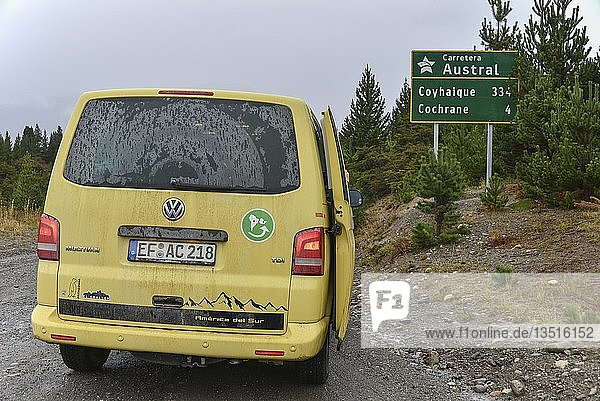 Yellow travel minibus on the Carretera Austral at Cochrane at road sign  Patagonia  Chile  South America