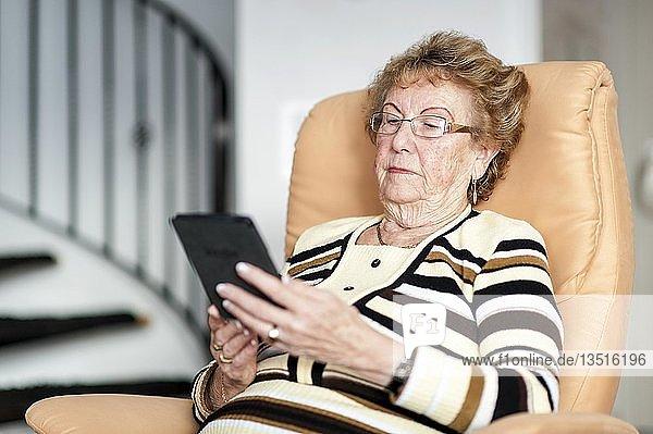 Seniorin sitzt in einem Sessel und liest in einem eBook  Deutschland  Europa