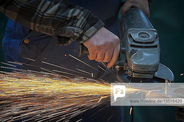 Hände eines Arbeiters führen einen Trennschleifer