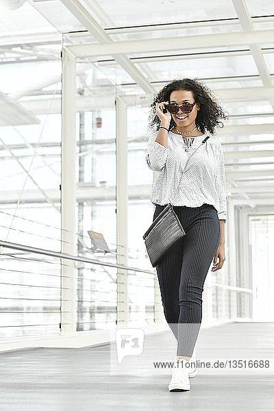 Junge Frau  schaut neckisch  geht durch Glastunnel  Deutschland  Europa