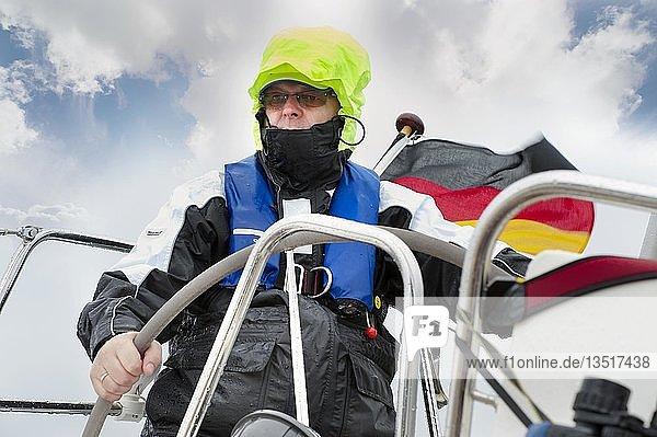 Skipper steht am Ruder einer Segelyacht