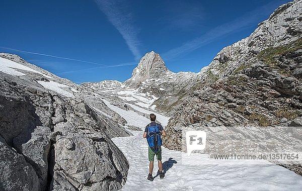 Wanderer auf Schneefeld  Wanderweg zur Wasseralm über Niederbrunnsulzen  hinten WIldalmrotenkopf  Steinernes Meer im Frühling mit Schnee  Nationalpark Berchtesgaden  Bayern  Deutschland  Europa