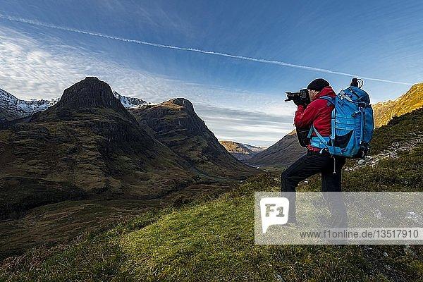 Photographer in mountain landscape with peaks of Stob Coire nan Lochan,  Glen Coe,  west Highlands,  Scotland,  United Kingdom,  Europe