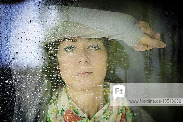 Junge Frau schaut bei Regenwetter durch das Fenster  Grevenbroich  Rheinland  Nordrhein-Westfalen  Deutschland  Europa