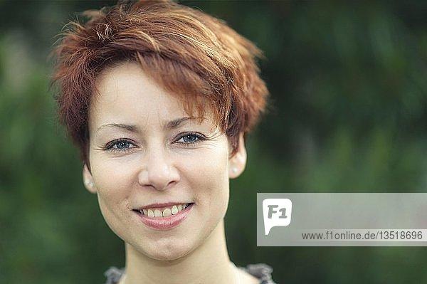 Lächelnde junge Frau mit kurzen roten Haaren  Portrait