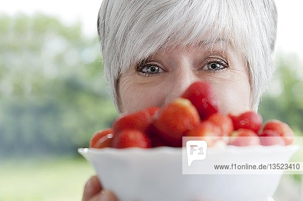 Frau präsentiert eine Schale mit frischen Erdbeeren