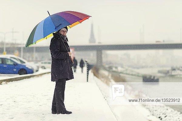 Frau steht mit buntem Regenschirm im Winter am Ufer des Rheins  Düsseldorf  Rheinland  Nordrhein-Westfalen  Deutschland  Europa