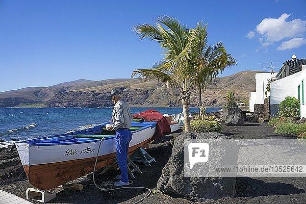Alter Fischer pflegt sein Boot im kleinen Fischerdorf Playa Quemada  Lanzarote  Kanarische Inseln  Spanien  Europa