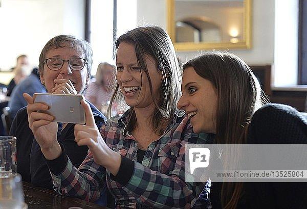 Junge Frauen und ältere Frau betrachten Smartphone  lachen  Portrait  Café  Stuttgart  Baden-Württemberg  Deutschland  Europa