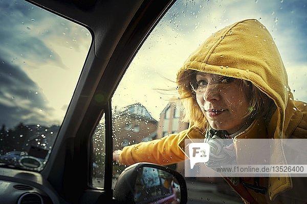 Junge Frau steht an einem PKW und zeigt die Fahrtrichtung an  Grevenbroich  Nordrhein-Westfalen  Deutschland  Europa