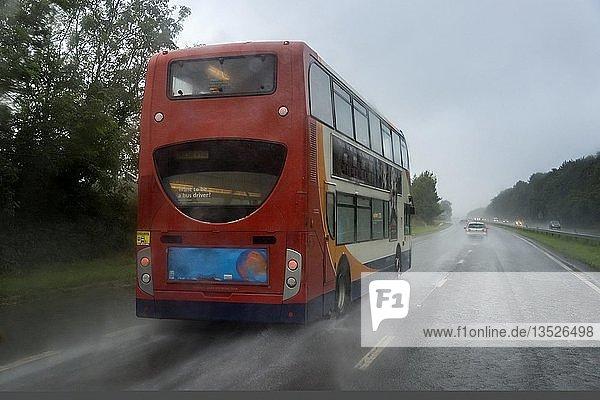 Roter Bus bei Regen auf der Autobahn  Cornwall  England  Großbritannien  Europa
