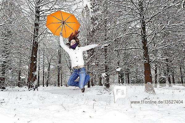 Junge Frau springt voller Freude im Winterwald in die Höhe