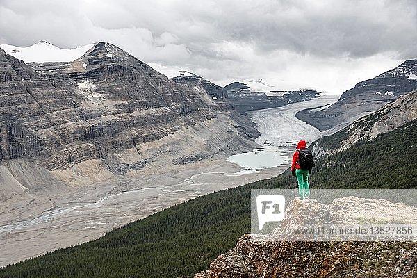Wanderin steht auf einem Felsen  Ausblick in Tal mit Gletscherzunge  Parker Ridge  Saskatchewan Gletscher  Athabasca Gletscher  Jasper National Park Nationalpark  Canadian Rocky Mountains  Alberta  Kanada  Nordamerika