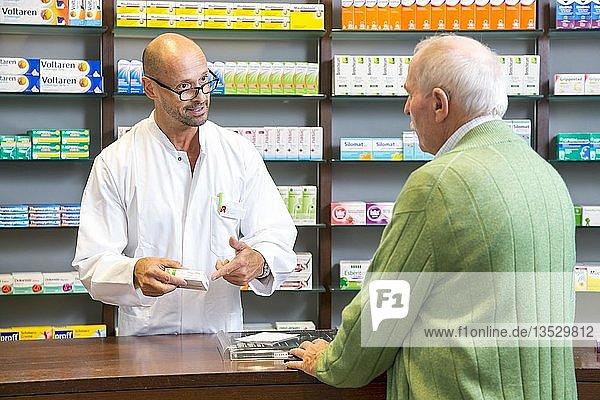 Apotheke  Apotheker berät einen Kunden  der ein Medikament auf Rezept abholt  Deutschland  Europa