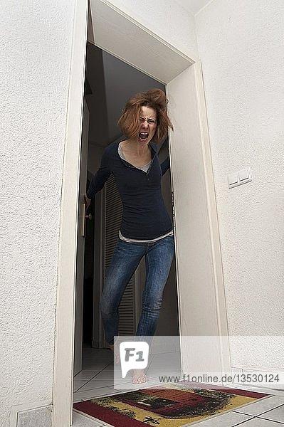 Junge Frau schreit wütend aus der Wohnungstür