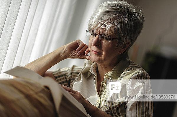 Seniorin sitzt am Fenster und liest ein Buch  Nordrhein-Westfalen  Deutschland  Europa