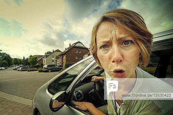 Wütende PKW-Fahrerin steckt den Kopf aus dem Fenster  Grevenbroich  Rheinland  Nordrhein-Westfalen  Deutschland  Europa