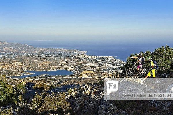 Zwei Mountainbiker stehen auf Aussichtspunkt mit Ausblick auf Lerapetra  bei Stavros  Selakano  Kreta  Griechenland  Europa