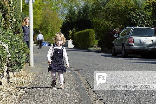 Kleines Mädchen geht allein auf dem Fußweg