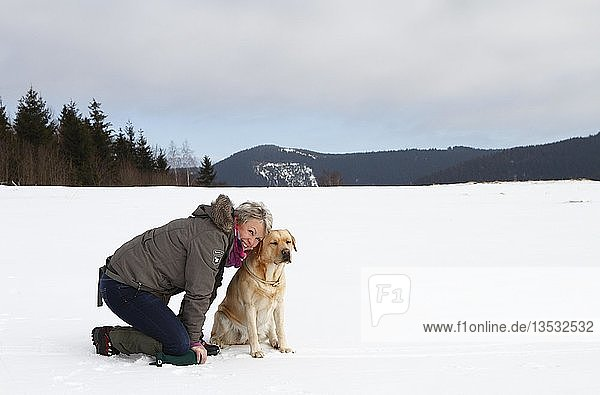 Woman with a Golden Retriever kneeling in the snow  Thuringia  Germany  Europe