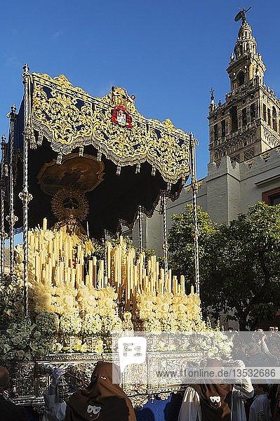 Büßer und dekorierter Wagen mit der gesegneten Jungfrau bei der Semana Santa Prozession  Karwoche  an der maurischen Giralda  Sevilla  Andalusien  Spanien  Europa