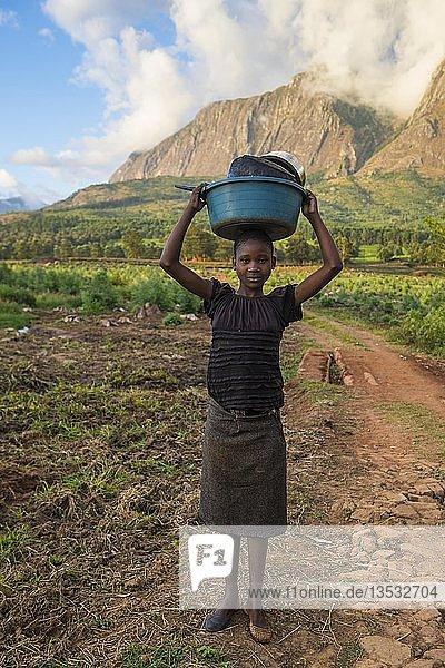 Mädchen mit gewaschenem Geschirr auf dem Kopf vor dem Mulanje Berg  Malawi  Afrika