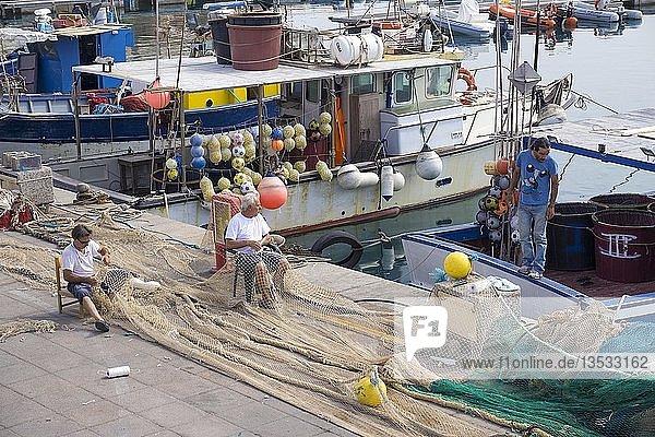 Fischer reparieren ihre Netze am Hafen  Ortsteil Isola Rossa  Trinità d?Agultu e Vignola  Provinz Sassari  Sardinien  Italien  Europa