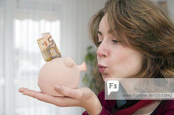 Junge Frau küsst ihr Sparschwein