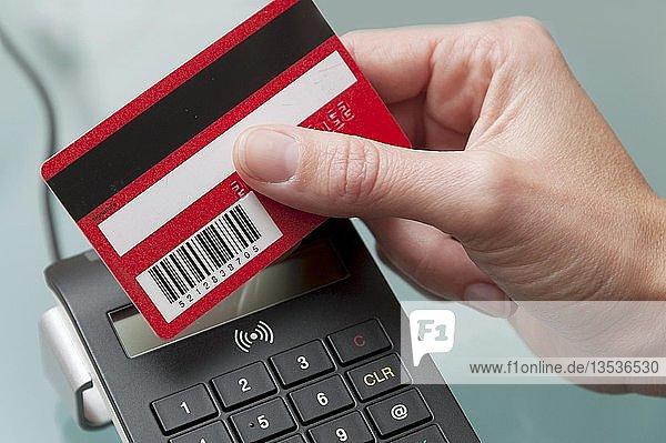 Eine Hand hält eine elektronische Karte an ein Lesegerät