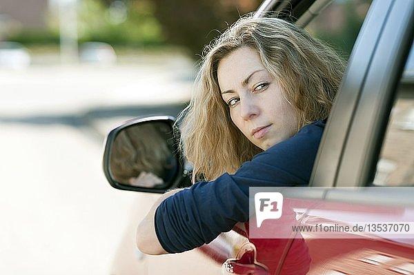 Junge Frau schaut aus dem Fenster eines PKW