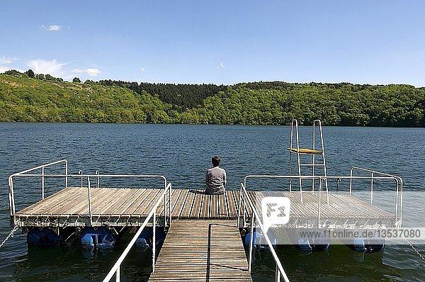 Frau sitzt auf Ponton ud blickt auf See  Puy de Dome  Auvergne  Frankreich  Europa