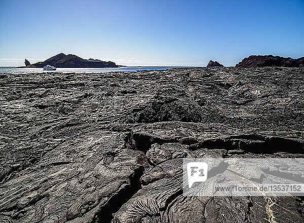 View over black volvanic rocks  lava field in Sullivan Bay towards Bartolome Island  Santiago or James Island  Galapagos  Ecuador  South America