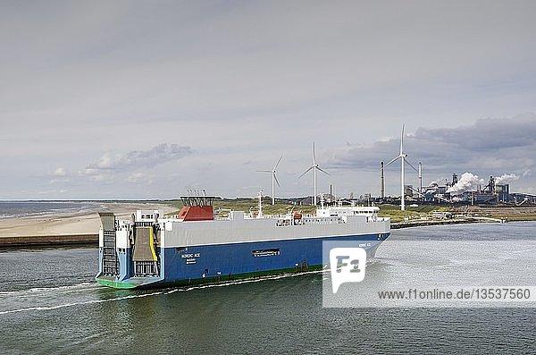 Autotransportschiff Nordic Ace läuft in den Hafen von Ijmuiden ein  dahinter Windräder und Industrieanlagen  Nordholland  Niederlande  Europa