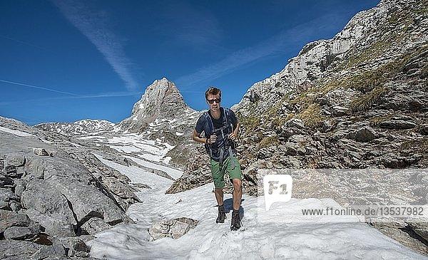 Wanderer im Schneefeld  Wanderweg zur Wasseralm über Niederbrunnsulzen  hinten Wildalmrotenkopf  Steinernes Meer im Frühling mit Schnee  Nationalpark Berchtesgaden  Bayern  Deutschland  Europa