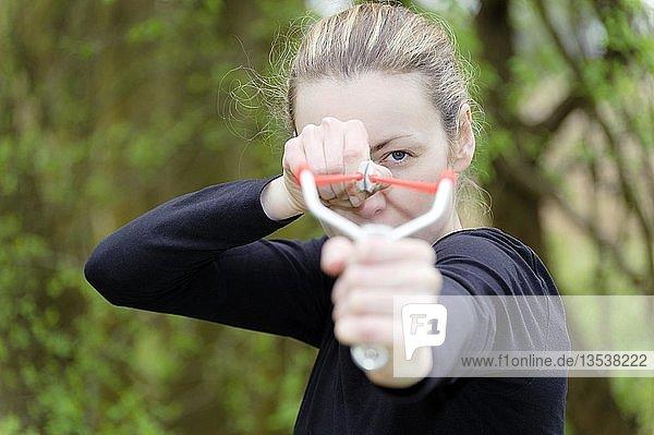Junge Frau zielt mit einem Katapult  Zwille