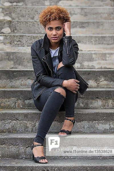 Junge dunkle Frau sitzt auf einer Steintreppe  Fashion  Portrait