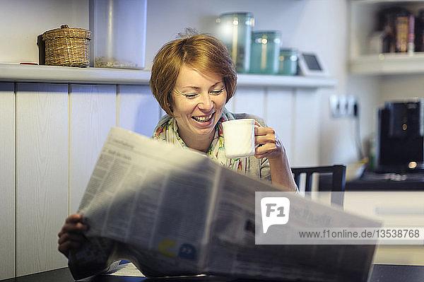 Frau sitzt am Küchentisch und liest lachend die Zeitung  Deutschland  Europa