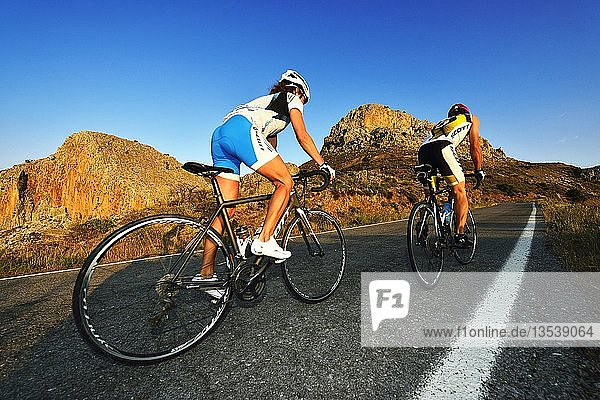 Zwei Rennradfahrer radeln bergauf auf der Straße  Mesara-Hochebene bei Zaros  Kreta  Griechenland  Europa