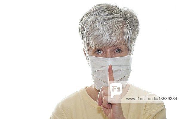 Frau mit Mundschutz und erhobenem Zeigefinger