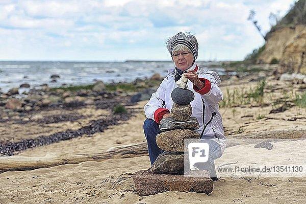 Eine Frau baut am Strand eine Steinpyramide  Timmendorf auf der Insel Poel  Mecklenburg-Vorpommern  Deutschland  Europa