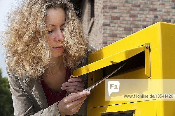 Junge Frau wirft Brief in einen Briefkasten