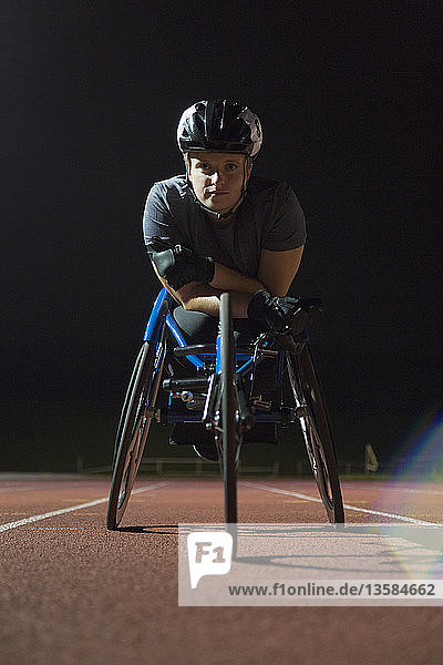 Portrait determined  tough young female paraplegic athlete training for wheelchair race on sports track at night