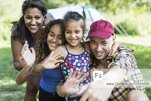Happy family waving  taking selfie with camera phone at campsite