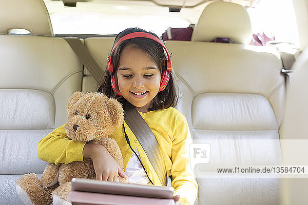 Smiling girl with teddy bear using digital tablet with headphones in back seat of car